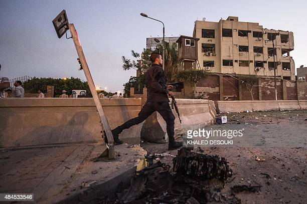 An Egyptian policeman runs past some of the remains of a car which exploded in front of a national security building in northern Cairo's district of...