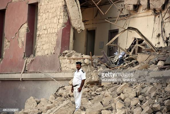 An Egyptian policeman stands in the rubble at the site of a powerful bomb explosion that ripped through the Italian consulate killing one person in...