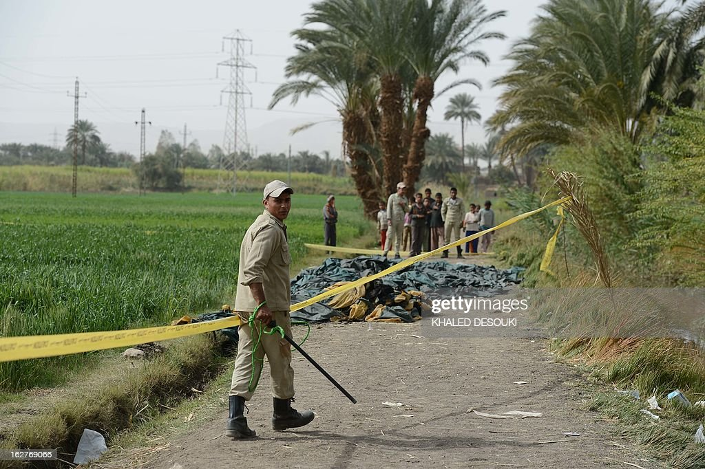 An Egyptian policeman walks at the site of a hot air balloon accident in Luxor on February 26, 2013. A hot air balloon exploded and plunged to earth at Egypt's ancient temple city of Luxor during a sunrise flight, killing up to 19 tourists, including Asians and Europeans, sources said. AFP PHOTO / KHALED DESOUKI