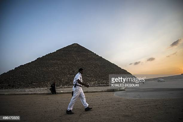 An Egyptian policeman walks in front Giza's Pyramid of Khufu on the southern outskirts of Cairo on November 9 2015 Moscow acknowledged on November 10...