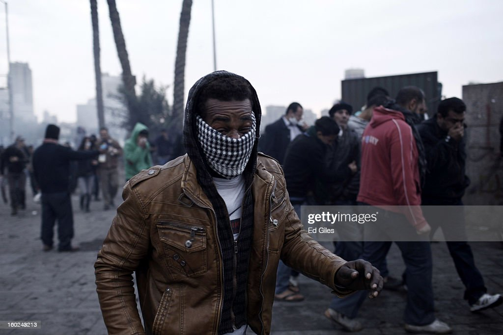 An Egyptian protester affected by exposure to tear gas walks away from clashes between protesters and Egyptian riot police near Tahrir Square on January 28, 2013 in Cairo, Egypt. Violent protests continued across Egypt three days after the second anniversary of the Egyptian Revolution that overthrew former President Hosni Mubarak and two days after 21 men were sentenced to death in connection with the deaths of 74 football fans during riots at Port Said stadium one year ago.