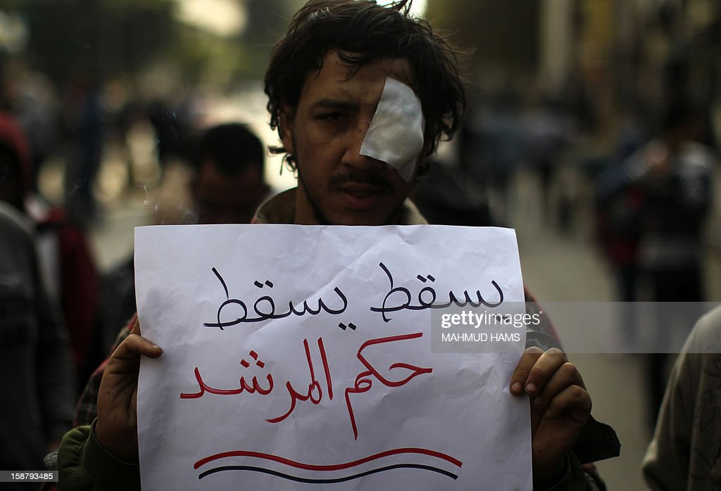An Egyptian protester against Egypt's President Mohamed Morsi carries a placard which reads in Arabic 'Down with the morshid's rule' during a demonstration in front of the Shura Council, the upper house of parliament where the Constituent Assembly drafted the country's new constitution, as Morsi gives a speech before a newly empowered senate in Cairo on December 29, 2012. Morsi said in the address, a disputed new constitution guaranteed equality for all Egyptians, and downplayed the country's economic woes.