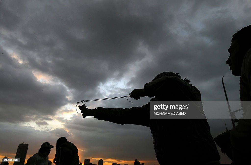 An Egyptian protester aims a slingshot during clashes with riot police near Cairo's Tahrir Square on January 29, 2013. Egypt's military chief warned that the political crisis sweeping the country could lead to the collapse of the state, as thousands defied curfews and the death toll from days of rioting rose to 52.
