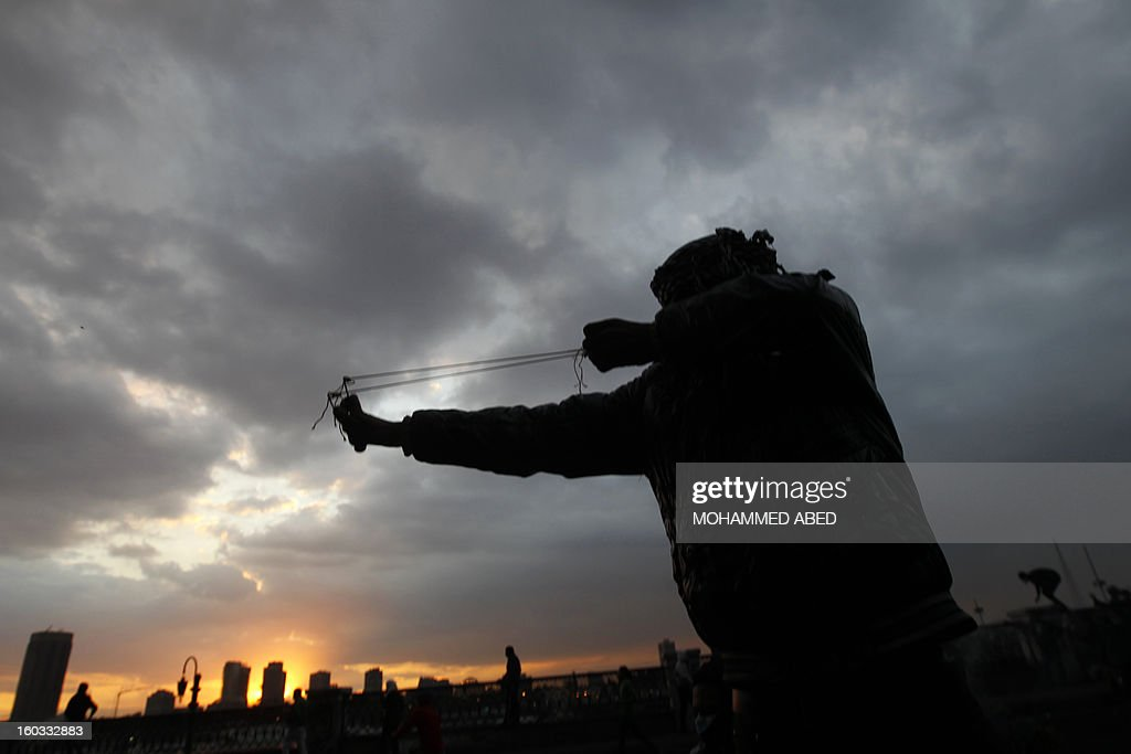 An Egyptian protester aims a slingshot during clashes with riot police near Cairo's Tahrir Square on January 29, 2013. Egypt's military chief warned that the political crisis sweeping the country could lead to the collapse of the state, as thousands defied curfews and the death toll from days of rioting rose to 52. AFP PHOTO/MOHAMMED ABED