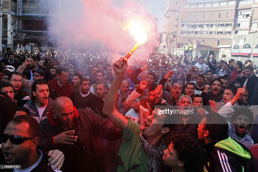 An Egyptian protester and fan of alMasry football club waves a flare as others chant slogans during a demonstration in front of the prison in the...