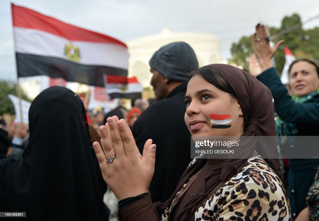 An Egyptian protester applauds during a demonstration in a show of opposition to Morsi and his Muslim Brotherhood in front of the Presidential palace in Cairo on February 1, 2013. Egyptian security used water cannon and fired shots into the air as protesters threw petrol bombs and stones into the grounds of the presidential palace, an AFP correspondent said.