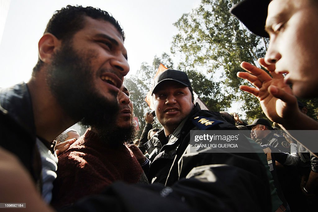 An Egyptian protester argues with a riot policeman during a demonstration organised by Egyptian Islamists against the French intervention in Mali on January 18, 2013 in Cairo. The brother of Al-Qaeda chief Ayman al-Zawahiri joined dozens of Egyptian Islamists in a protest near the French embassy in Cairo. AFP PHOTO/GIANLUIGI GUERCIA