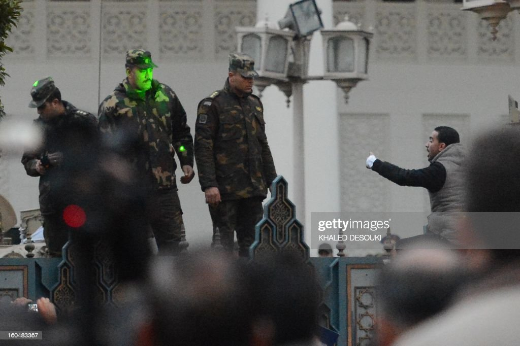 An Egyptian protester argues with presidential guards who stand behind the presidential palace's gate during a protest in front of it in a show of opposition to Morsi and his Muslim Brotherhood on February 1, 2013 in Cairo. Egyptian security used water cannon and fired shots into the air as protesters threw petrol bombs and stones into the grounds of the presidential palace, an AFP correspondent said.