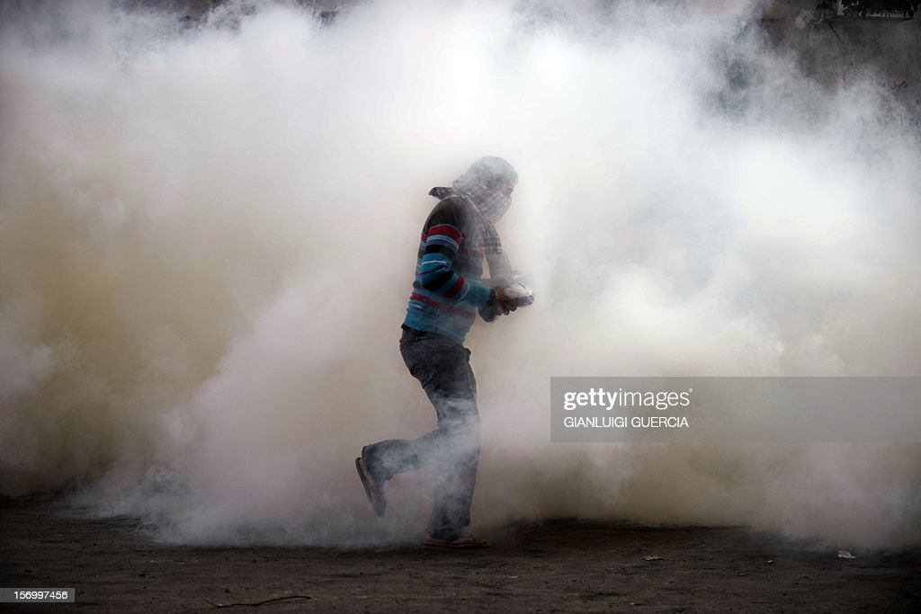 An Egyptian protester attempts to throw back a tear gas canister on November 27, 2012 during clashes with the Egyptian Riot Police in Omar Makram street, off Tahrir Square in Cairo. Clashes between police and protesting youths erupted on Tuesday near Cairo's Tahrir Square, ahead of a mass rally against a decree by President Mohamed Morsi granting himself broad powers. The planned demonstrations come a day after Morsi stuck by his controversial decree in a meeting with judges that was aimed at defusing the worst political crisis since his election in June.