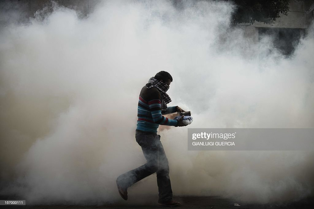 An Egyptian protester attempts to throw back a tear gas canister on November 27, 2012 during clashes with the Egyptian Riot Police in Omar Makram street, off Tahrir Square in Cairo. Clashes between police and protesting youths erupted on Tuesday near Cairo's Tahrir Square, ahead of a mass rally against a decree by President Mohamed Morsi granting himself broad powers. The planned demonstrations come a day after Morsi stuck by his controversial decree in a meeting with judges that was aimed at defusing the worst political crisis since his election in June. GUERCIA