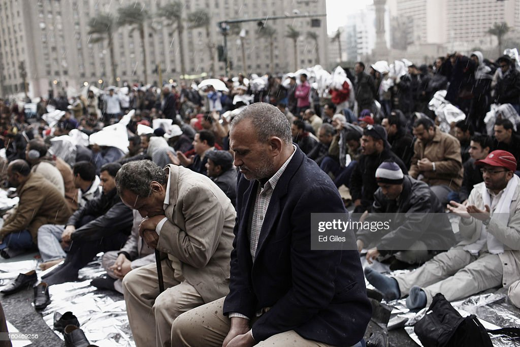 An Egyptian protester attends midday prayers in the midst of a rain storm during a protest against Egyptian President Mohammed Morsi in Tahrir Square on February 1, 2013 in Cairo, Egypt. Protests continued across Egypt nearly one week after the second anniversary of the Egyptian Revolution that overthrew former President Hosni Mubarak on January 25, 2011. Further protests are expected Friday to commemorate the first anniversary of the Port Said football massace, when over 70 fans of the Cairo-based Al Ahly football club were killed in a violent post-match brawl between fans of the opposing teams inside the Port Said football stadium after a match between the Al Ahly and Al Masry football teams. (Photo by Ed Giles/Getty Images).