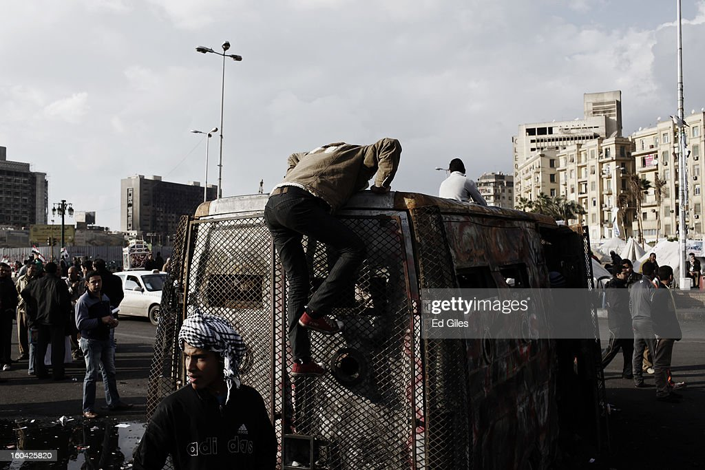 An Egyptian protester climbs on top of a destroyed armoured vehicle of the Egyptian Central Security Forces stolen and burnt in earlier clashes between protesters and riot police nearby, in Tahrir Square on January 31, 2013 in Cairo, Egypt. Protests continued across Egypt nearly one week after the second anniversary of the Egyptian Revolution that overthrew former President Hosni Mubarak on January 25, 2011. Further protests are expected over the coming weekend to commemorate the first anniversary of the Port Said football massacre, when over 70 fans of the Cairo-based Al Ahly football club were killed in a violent post-match brawl between fans of the opposing teams inside the Port Said football stadium after a match between the Al Ahly and Al Masry football teams.