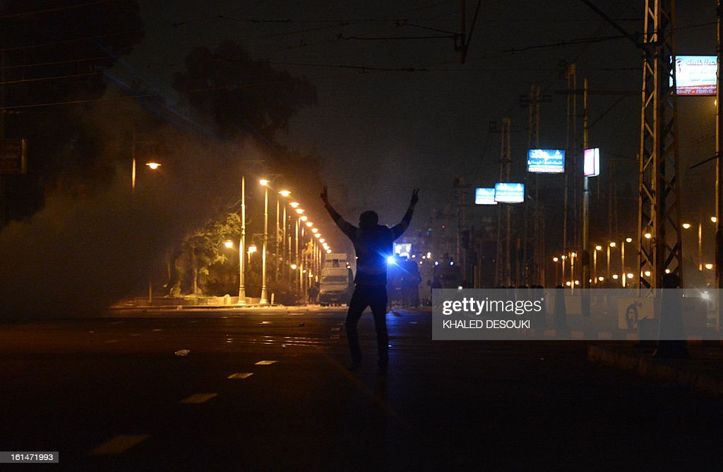 An Egyptian protester confronts riot police in front of the presidential palace in Cairo, on February 11, 2013. Egyptian police fired tear gas and water cannon at stone-throwing protesters outside the presidential palace as the opposition held rallies to mark the second anniversary of Hosni Mubarak's overthrow. AFP PHOTO / KHALED DESOUKI