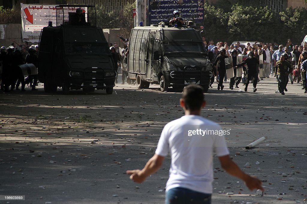 An Egyptian protester faces riot Police during clashes at Tahrir square on November 25, 2012 in Cairo. Egypt's powerful Muslim Brotherhood called nationwide demonstrations today in support of Islamist President Mohamed Morsi in his showdown with the judges over the path to a new constitution.