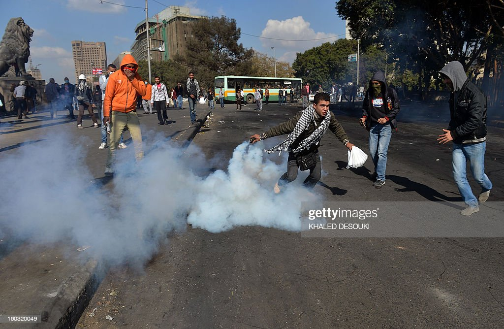 An Egyptian protester forwards back a tear gas canister fired by riot police during clashes near Cairo's Tahrir Square on January 29, 2013. Egypt's military chief warned that the political crisis sweeping the country could lead to the collapse of the state, as thousands defied curfews and the death toll from days of rioting rose to 52.