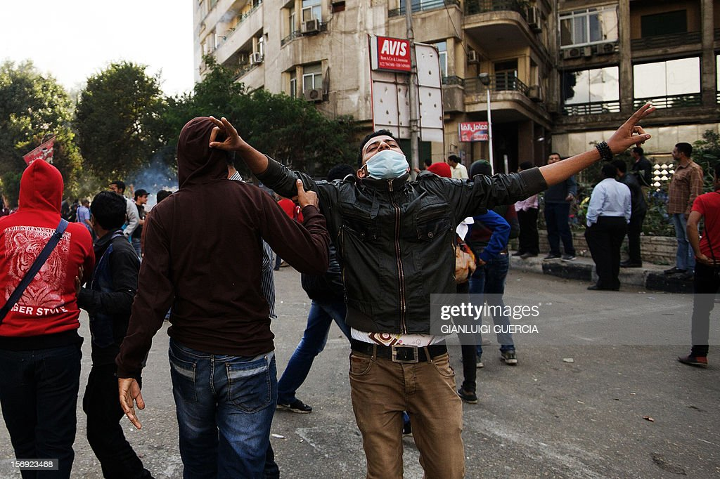 An Egyptian protester gestures during clashes with Egyptian riot Police during clashes at Simon Bolivar square on November 25, 2012 in Cairo. Egypt's powerful Muslim Brotherhood called nationwide demonstrations today in support of Islamist President Mohamed Morsi in his showdown with the judges over the path to a new constitution.