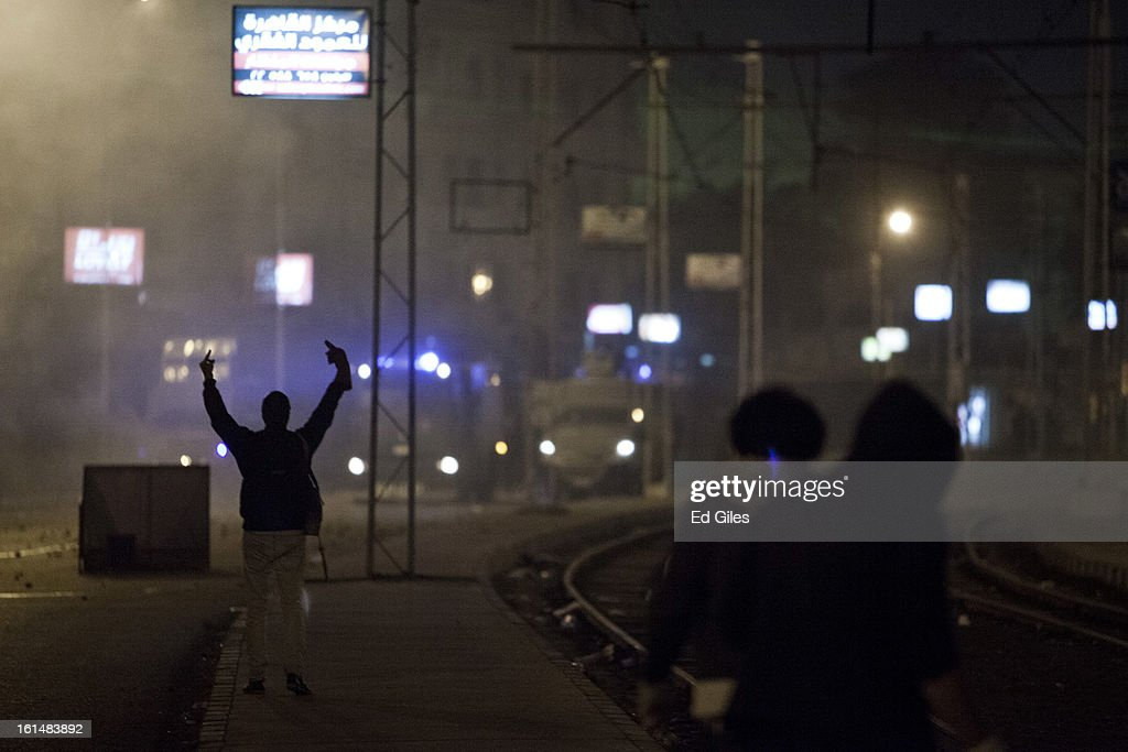 An Egyptian protester gestures toward nearby Egyptian riot police during violent protests by the Presidential Palace in Heliopolis, February 11, 2013 in Cairo, Egypt. Protests continued across Egypt against President Morsi and the Muslim Brotherhood on the 2nd anniversary of former President Hosni Mubarak stepping down, and over two weeks after the second anniversary of the Egyptian Revolution beginning on January 25, 2011. (Photo by Ed Giles/Getty Images).