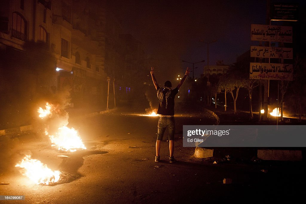 An Egyptian protester gestures toward nearby riot police during clashes with Egyptian security forces near the headquarters of the Muslim Brotherhood on March 22, 2013 in Cairo, Egypt. Clashes continued between opposition protesters and both Egyptian security forces and supporters of the Muslim Brotherhood into the night. Opposition demonstrators converged on the headquarters of the Muslim Brotherhood in the Cairo suburb of Muqattam to protest against the government of President Mohammed Morsi, who is closely connected to the Muslim Brotherhood movement.