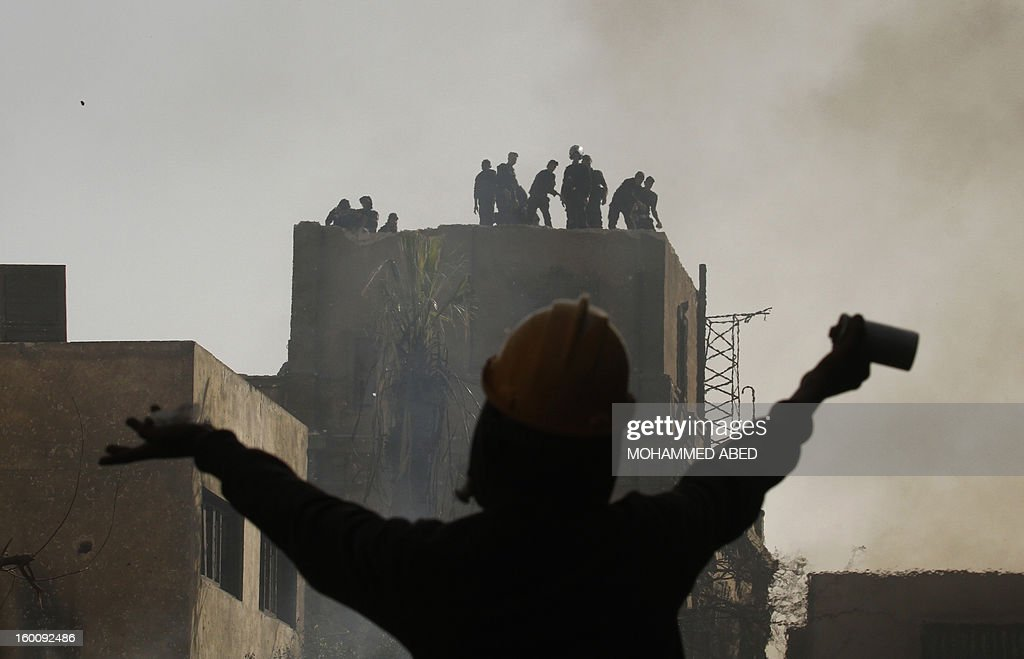 An Egyptian protester gestures towards riot police during a demonsration in Cairo's Tahrir Square on January 26, 2013. Egypt's Islamist President Mohamed Morsi appealed for calm after at least seven people were killed in violence on the second anniversary of the revolution that ousted Hosni Mubarak.