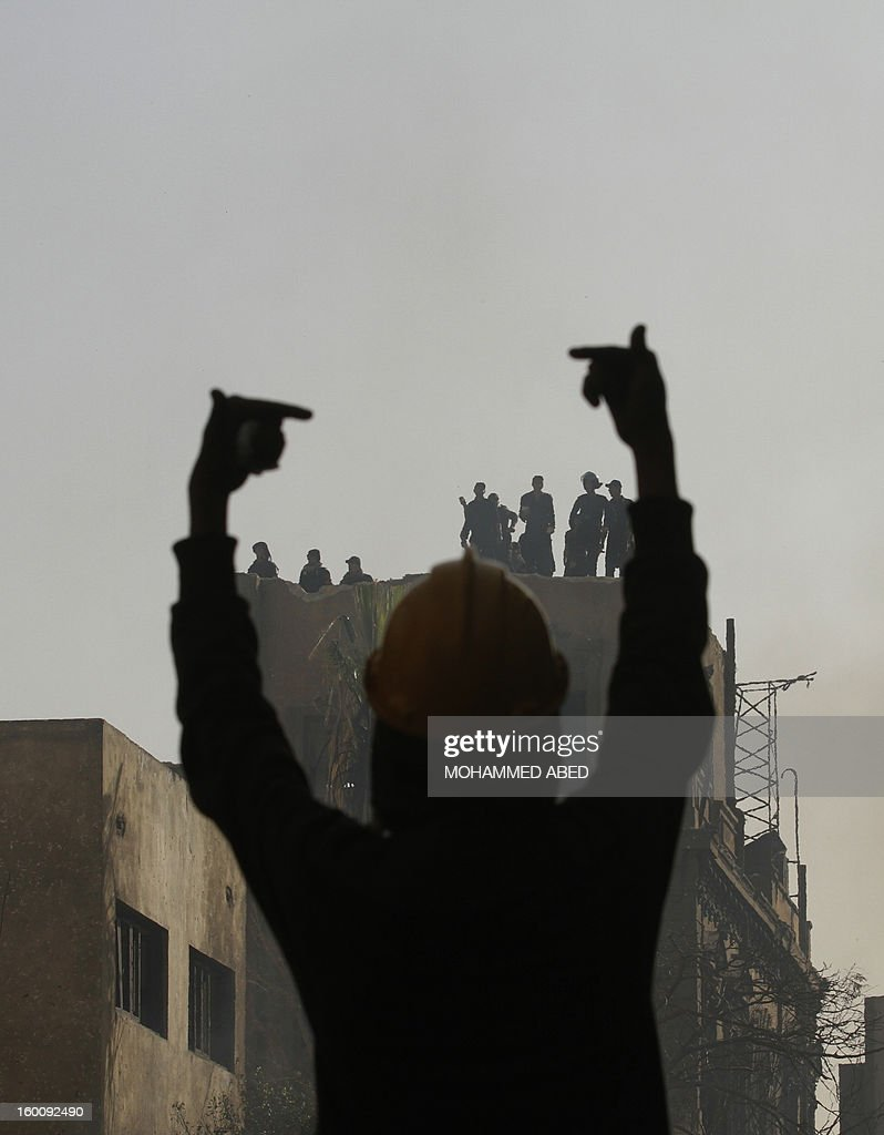 An Egyptian protester gestures towards riot police during a demonsration in Cairo's Tahrir Square on January 26, 2013. Egypt's Islamist President Mohamed Morsi appealed for calm after at least seven people were killed in violence on the second anniversary of the revolution that ousted Hosni Mubarak. AFP PHOTO/MOHAMMED ABED