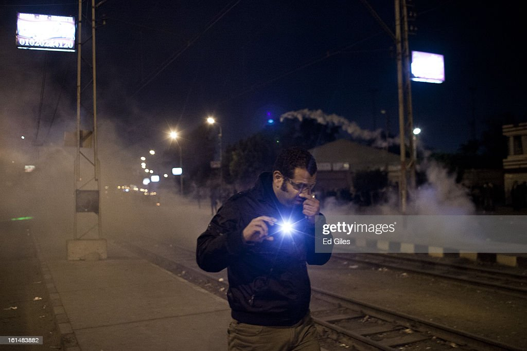 An Egyptian protester holding a mobile phone walks away from tear gas fired by nearby Egyptian riot police during violent protests by the Presidential Palace in Heliopolis, February 11, 2013 in Cairo, Egypt. Protests continued across Egypt against President Morsi and the Muslim Brotherhood on the 2nd anniversary of former President Hosni Mubarak stepping down, and over two weeks after the second anniversary of the Egyptian Revolution beginning on January 25, 2011. (Photo by Ed Giles/Getty Images).