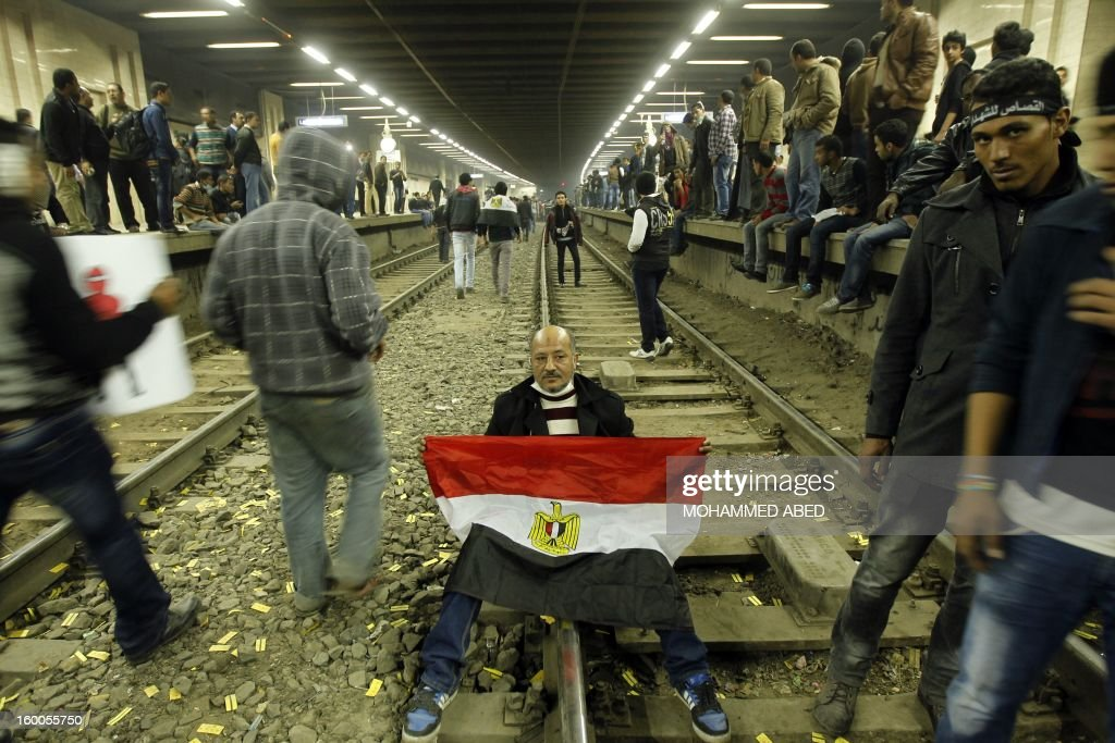 An Egyptian protester holding his national flag sits on the tracks of the metro in Cairo's landmark Tahrir Square after demonstrators closed it down on January 25, 2013. Egyptian protesters stormed a regional government headquarters and clashed with police as mass rallies shook the country on the second anniversary of an uprising that ousted Hosni Mubarak and ushered in Islamic rule.