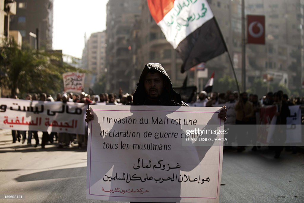 An Egyptian protester holds a banner that reads in Arabic 'Your invasion of Mali is a declaration of war against all Muslims' during a demonstration organised by Egyptian Islamists against the French intervention in Mali on January 18, 2013 in Cairo. The brother of Al-Qaeda chief Ayman al-Zawahiri joined dozens of Egyptian Islamists in a protest near the French embassy in Cairo. AFP PHOTO/GIANLUIGI GUERCIA