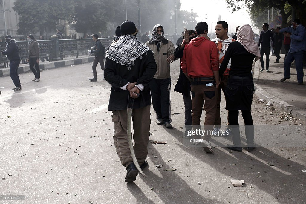 An Egyptian protester holds a homemade sword behind his back during a demonstration in Tahrir Square on January 27, 2013 in Cairo, Egypt. Violent protests continued across Egypt two days after the second anniversary of the Egyptian Revolution that overthrew former President Hosni Mubarak on January 25, and one day after the announcement of the death penalty for 21 suspects in connection with a football stadium massacre one year before. The verdict was announced in a case over the deaths of more than seventy fans of Egypt's Al-Ahly football club in a stadium massacre on February 1, 2012, in the northern city of Port Said, during a brawl that began minutes after the final whistle of a match between Al-Ahly and opposing side, Al-Masry. 21 fans of the opposing side, Al-Masry, were given the death penalty, a verdict that must now be approved by Egypt's Grand Mufti. (Photo by Ed Giles/Getty Images).