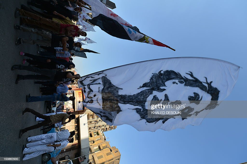 An Egyptian protester holds a huge portrait of Mina Daniel, an activist who was killed during the protests last October, during a march in Cairo on October 9, 2012 to mark one year since nearly 30 demonstrators were killed in a Coptic Christian demonstration that was violently crushed by security forces. On October 9, 2011, thousands of demonstrators marched from the neighborhood of Shubra to Maspero to denounce the torching of a church in the southern province of Aswan. The protest was attacked and violence flared when the army and riot police charged at the protesters, leaving 26 Coptic Christians, one Muslim man and one policeman dead, says Amnesty International.