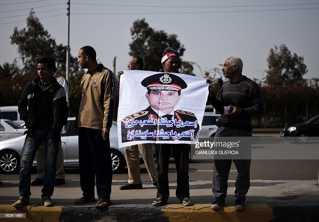 An Egyptian protester holds a picture of defence minister and commander of the armed forces, General Abdel Fattah al-Sissi, with a slogan reading in Arabic 'Wake up army, the people are sad. Wake up army, in whose hands have you left us' during a demonstration in support of the Egyptian army and against the Muslim Brotherhood in Cairo on March 1, 2013. On almost every Friday -- the first day of the Egyptian weekend -- opposition groups have called protests against President Mohamed Morsi and his powerful Muslim Brotherhood, which have regularly degenerated into violence.