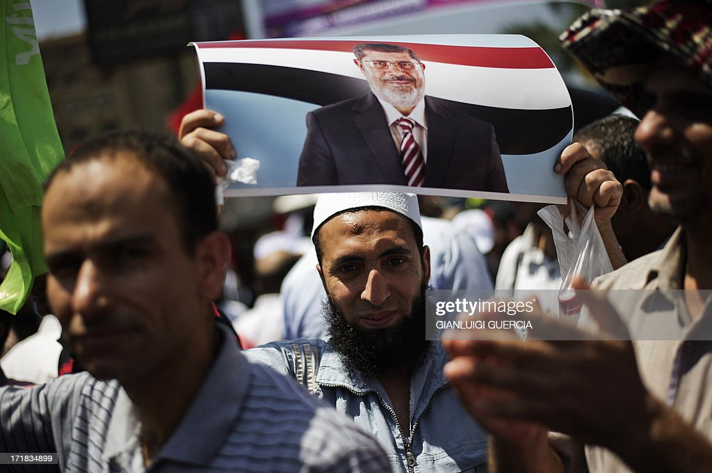 An Egyptian protester holds a picture of President Mohamed Morsi as Islamists and Muslim Brotherhood supporters gather at the Rabaa al-Adawiya mosque to start an open-ended sit-in in support of Morsi's legitimacy in Cairo on June 28, 2013. Supporters and opponents of Egypt's Islamist President Mohamed Morsi gathered for rival demonstrations, raising fears of fresh violence after one activist was killed overnight.