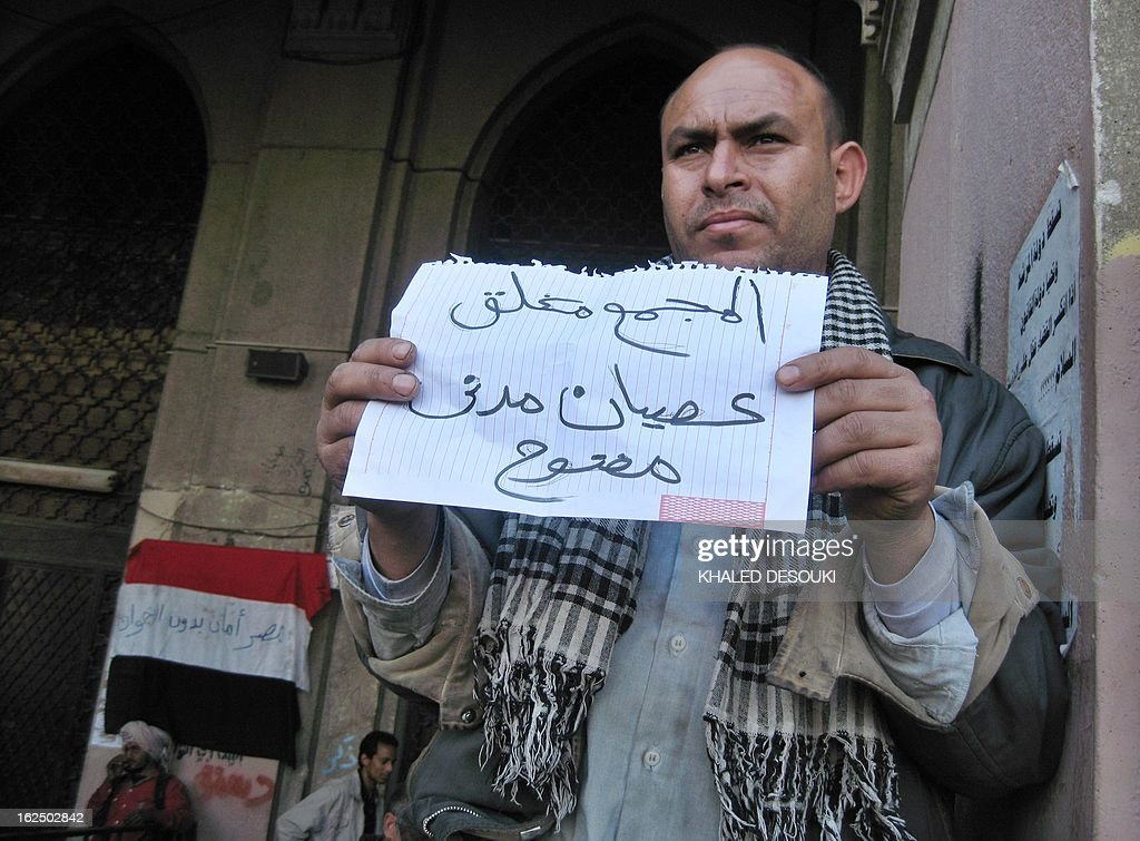 An Egyptian Protester holds a placard reading in Arabic 'The Mugamma is closed, open civil disobedience'' in front of Cairo's main administrative building on February 24, 2013, as they closed its doors part of a growing campaign of civil disobedience around the country. A group of protesters closed the doors of the Mugamma, a massive labyrinth of bureaucratic offices on the edge of Tahrir Square, leaving only a side exit for employees to leave. On the national flag (background) is written 'Egypt is moor safe witout Muslim Brotherhoods''.