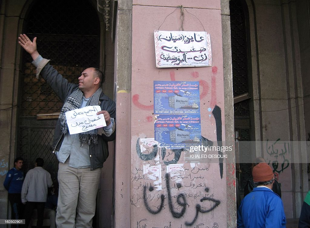 An Egyptian Protester holds a placard reading in Arabic 'The Mugamma is closed, open civil disobedience'' in front of Cairo's main administrative building on February 24, 2013, as they closed its doors part of a growing campaign of civil disobedience around the country. A group of protesters closed the doors of the Mugamma, a massive labyrinth of bureaucratic offices on the edge of Tahrir Square, leaving only a side exit for employees to leave. AFP PHOTO KHALED DESOUKI