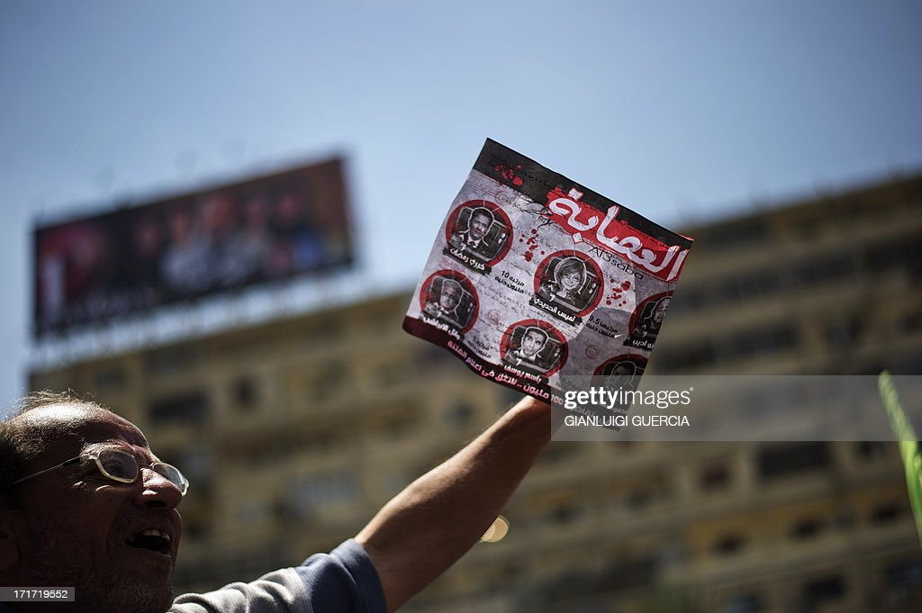 An Egyptian protester holds a poster against television presenters and journalists as Islamists and Muslim Brotherhood supporters gather at the Rabaa al-Adawiya mosque to start an open-ended sit-in in support of President Mohamed Morsi's legitimacy in Cairo on June 28, 2013. Supporters and opponents of Egypt's Islamist President Mohamed Morsi gathered for rival demonstrations, raising fears of fresh violence after one activist was killed overnight.