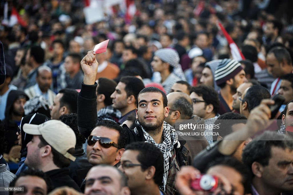 An Egyptian protester holds a red card similar to the one used in football as thousands gather near the presidential palace in Cairo to protest against a draft constitution and President Mohamed Morsi's sweeping powers decree on December 7, 2012. Thousands of protesters converged on the presidential palace in Cairo in a fresh bid to convince Morsi to give up what they see as dictatorial powers, and to postpone a referendum on a controversial new constitution.