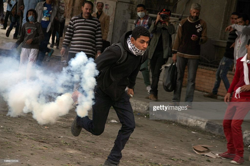 An Egyptian protester holds a tear gas canister during clashes with Egytptian riot police in Tahrir square on November 25, 2012 in Cairo. Egypt's powerful Muslim Brotherhood called nationwide demonstrations Sunday in support of Islamist President Mohamed Morsi in his showdown with the judges over the path to a new constitution. AFP PHOTO