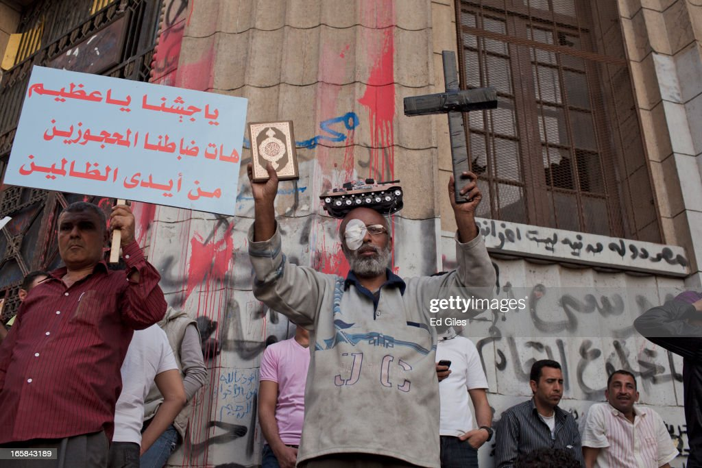 An Egyptian protester holds up a cross and a copy of the Koran during a demonstration at the Cairo High Court building against Egyptian President Mohammed Morsi and the government of the Muslim Brotherhood on April 6, 2013 in Cairo, Egypt. Hundreds of protesters gathered at multiple locations across Cairo and other cities in Egypt to mark the fifth anniversary of the April 6 movement, a major revolutionary group made up of youth and workers in Egypt. (Photo by Ed Giles/Getty Images).
