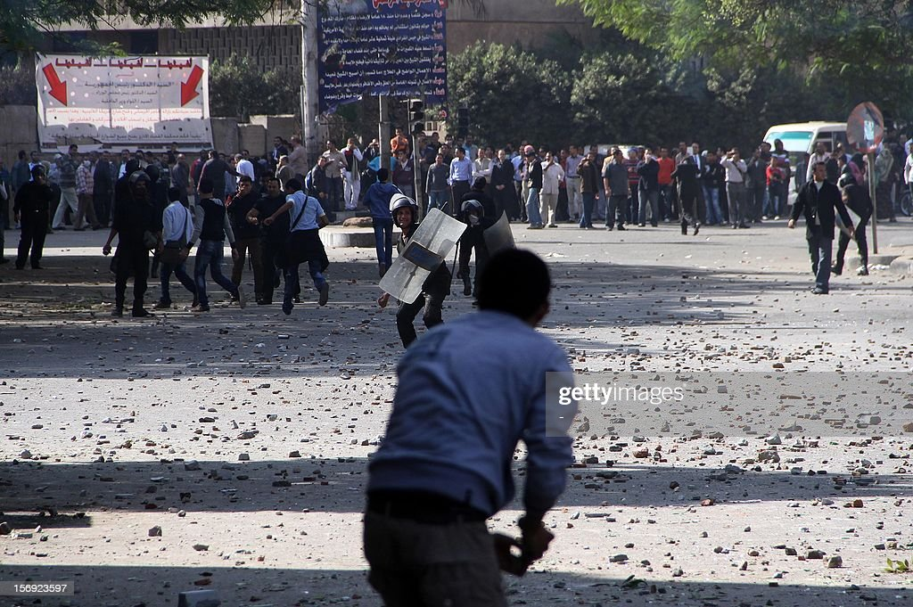An Egyptian protester hurls stones at riot Police during clashes at Tahrir square on November 25, 2012 in Cairo. Egypt's powerful Muslim Brotherhood called nationwide demonstrations today in support of Islamist President Mohamed Morsi in his showdown with the judges over the path to a new constitution.
