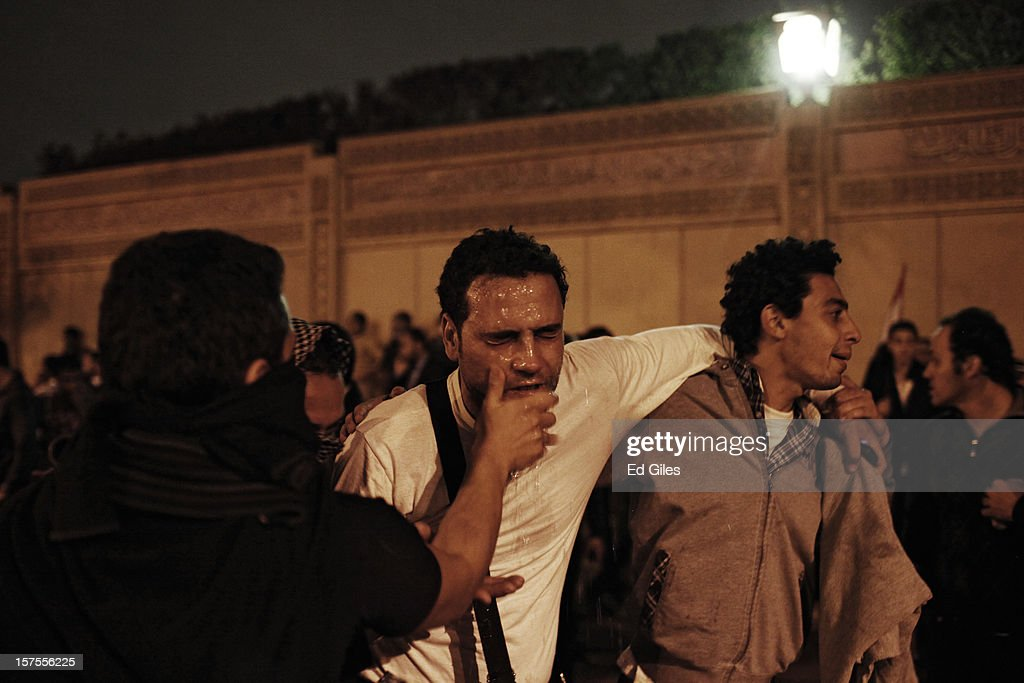 An Egyptian protester is helped by other protesters after exposure to tear gas fired by security forces during a protest against Egyptian President Mohammed Morsi at the Presidential Palace on December 4 in in Cairo, Egypt. Thousands of protesters converged on the Presidential Palace in the Cairo suburb of Heliopolis on Tuesday evening to demonstrate against the country's draft constitution that was rushed through parliament in an overnight session on November 29. Protesters and police briefly clashed outside the Presidential Palace before riot police retreated inside the palace grounds. The country's new draft constitution, passed by a constitutional assembly dominated by Islamists, will go to a referendum on December 15.
