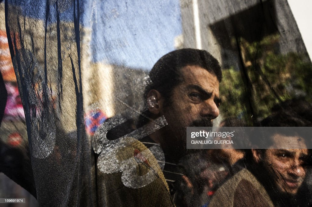 An Egyptian protester is seen through an Islamist flag during a demonstration organised by Egyptian Islamists against the French intervention in Mali on January 18, 2013 in Cairo. The brother of Al-Qaeda chief Ayman al-Zawahiri joined dozens of Egyptian Islamists in a protest near the French embassy in Cairo. AFP PHOTO/GIANLUIGI GUERCIA