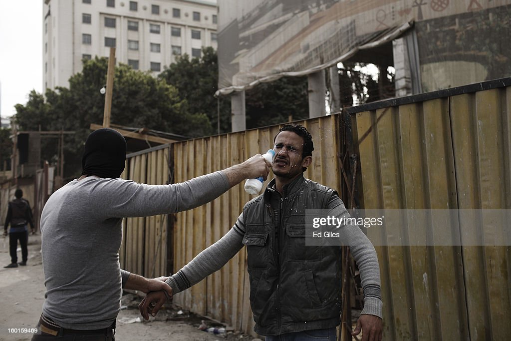 An Egyptian protester is treated for exposure to tear gas fired by riot police during a demonstration in Tahrir Square on January 27, 2013 in Cairo, Egypt. Violent protests continued across Egypt two days after the second anniversary of the Egyptian Revolution that overthrew former President Hosni Mubarak on January 25, and one day after the announcement of the death penalty for 21 suspects in connection with a football stadium massacre one year before. The verdict was announced in a case over the deaths of more than seventy fans of Egypt's Al-Ahly football club in a stadium massacre on February 1, 2012, in the northern city of Port Said, during a brawl that began minutes after the final whistle of a match between Al-Ahly and opposing side, Al-Masry. 21 fans of the opposing side, Al-Masry, were given the death penalty, a verdict that must now be approved by Egypt's Grand Mufti. (Photo by Ed Giles/Getty Images).