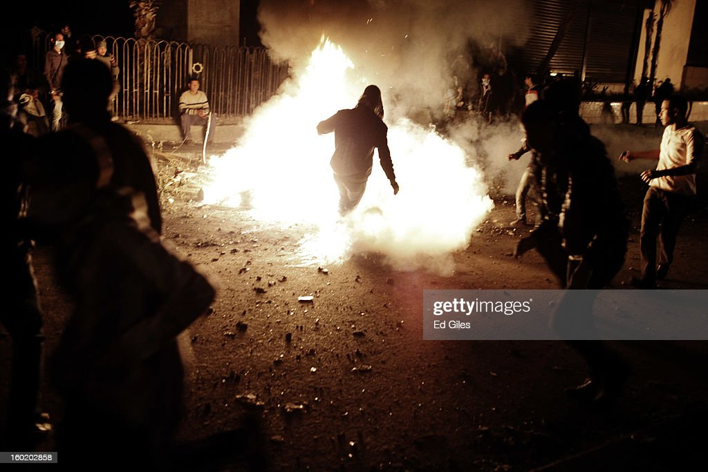 An Egyptian protester kicks a live tear gas canister into a fire during clashes with riot police near Tahrir Square on January 27, 2013 in Cairo, Egypt. Violent protests continued across Egypt two days after the second anniversary of the Egyptian Revolution that overthrew former President Hosni Mubarak on January 25, and one day after the announcement of the death penalty for 21 suspects in connection with a football stadium massacre one year before. The verdict was announced in a case over the deaths of more than seventy fans of Egypt's Al-Ahly football club in a stadium massacre on February 1, 2012, in the northern city of Port Said, during a brawl that began minutes after the final whistle of a match between Al-Ahly and opposing side, Al-Masry. 21 fans of the opposing side, Al-Masry, were given the death penalty, a verdict that must now be approved by Egypt's Grand Mufti. (Photo by Ed Giles/Getty Images).