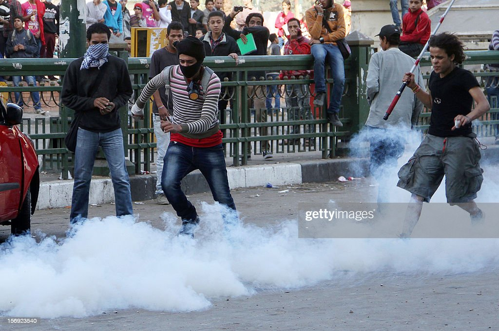 An Egyptian protester kicks a tear gas canister during clashes with Egytptian riot police in Tahrir square on November 25, 2012 in Cairo. Egypt's powerful Muslim Brotherhood called nationwide demonstrations Sunday in support of Islamist President Mohamed Morsi in his showdown with the judges over the path to a new constitution.