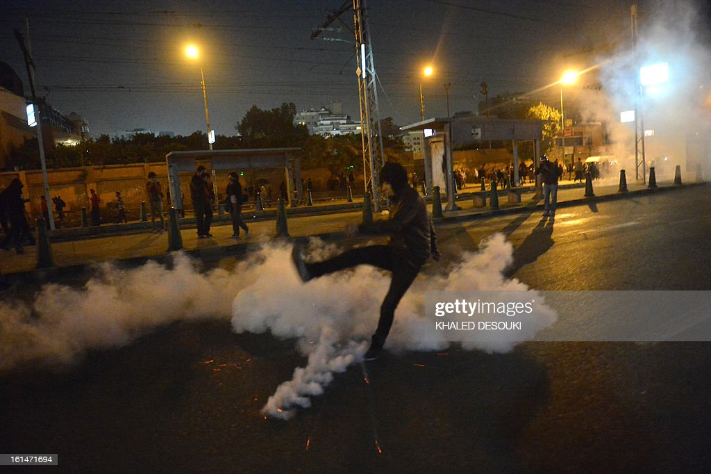 An Egyptian protester kicks a tear gas canister fired by riot police at stone-throwing protesters in front of the presidential palace in Cairo, on February 11, 2013, during opposition held rallies to mark the second anniversary of former president Hosni Mubarak's overthrow.