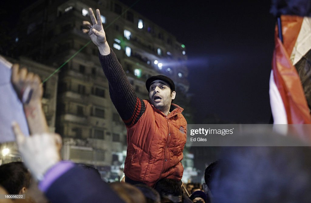 An Egyptian protester leads others in chants during a demonstration in Tahrir Square on January 25, in Cairo, Egypt. Thousands of protesters converged on the capital's iconic Tahrir Square on January 25, to mark the second anniversary of the overthrow of former President Hosni Mubarak's regime. (Photo by Ed Giles/Getty Images).