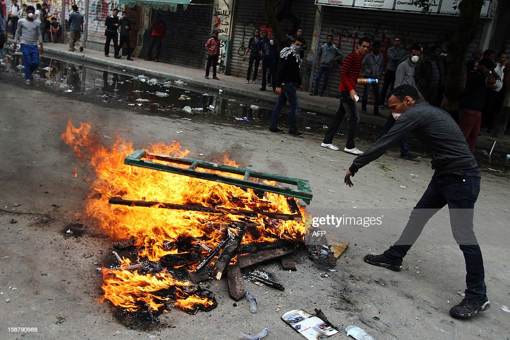 An Egyptian protester lights a bonfire in a street during clashes in Cairo on November 21, 2012. Egyptian protesters clashed with the police for a third day on the one year anniversary of deadly clashes that left 45 dead. At least 45 protesters died in the five days of street battles that began on November 19 last year to put pressure on the military, which took power after a popular uprising overthrew president Hosni Mubarak in February.