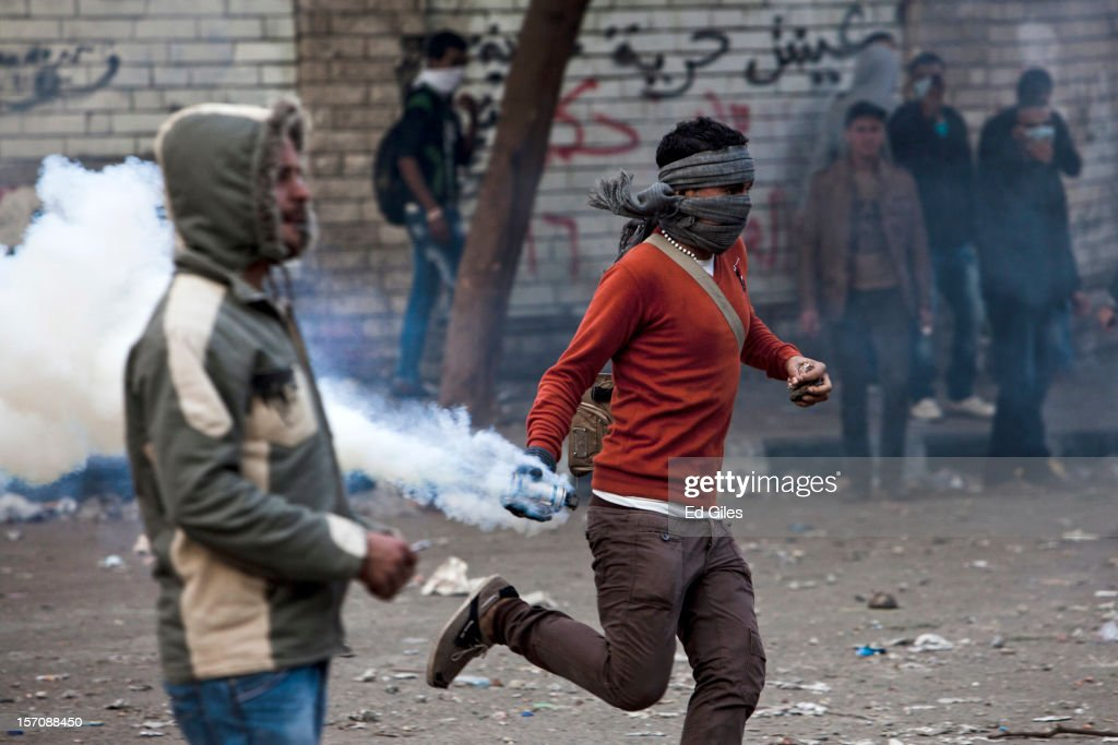 An Egyptian protester picks up a live tear gas round fired by riot police during demonstrations against Egyptian President Mohammed Mursi near Tahrir Square on November 28, 2012 in Cairo, Egypt. Demonstrations have been held after a week of tension and violent protest in response to Egyptian president Mohammed Mursi having awarded himself new constitutional powers, which many believe have been pushed through by the Muslim Brotherhood without inclusive consultation with other members of Egypt's cabinet and political leadership.