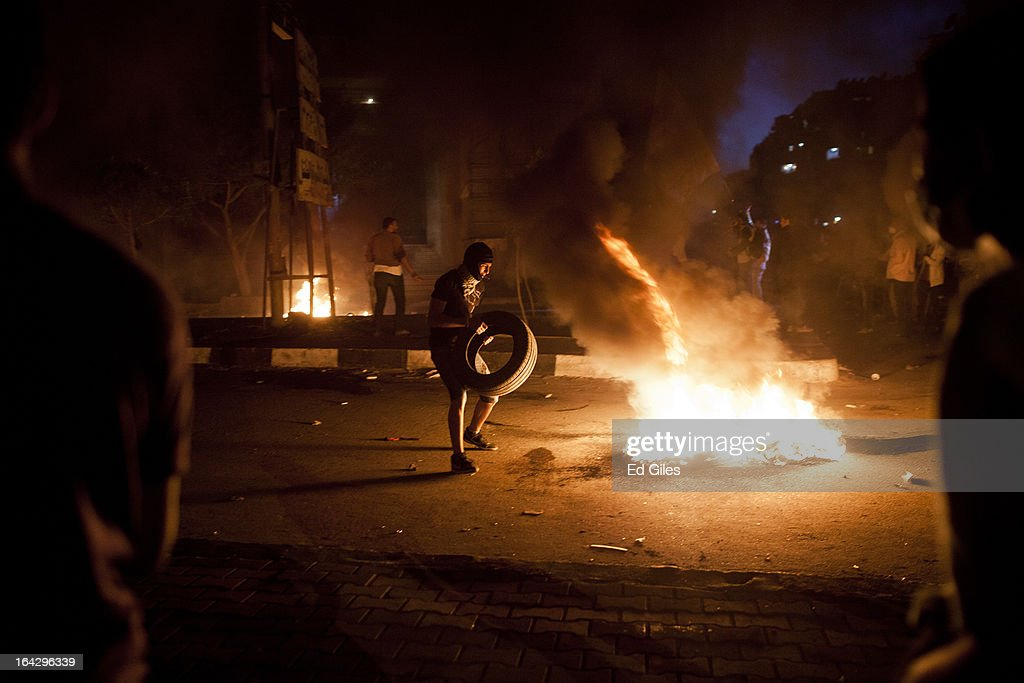 An Egyptian protester places a tire on a fire during clashes with Egyptian riot police near the headquarters of the Muslim Brotherhood on March 22, 2013 in Cairo, Egypt. Clashes continued between opposition protesters and both Egyptian security forces and supporters of the Muslim Brotherhood into the night. Opposition demonstrators converged on the headquarters of the Muslim Brotherhood in the Cairo suburb of Muqattam on Friday to protest against the government of President Mohammed Morsi, who is closely connected to the Muslim Brotherhood movement.