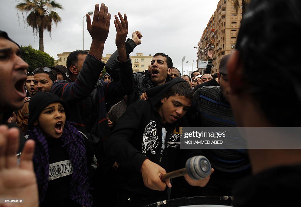An Egyptian protester plays a drum while others shout slogans against Egypt's President Mohamed Morsi during a demonstration after Friday prayers in the canal city of Port Said on February 1, 2013. Thousands of Egyptians flooded the streets in a show of opposition to the Islamist President and his Muslim Brotherhood after a week of a wave of deadly unrest swept the country.