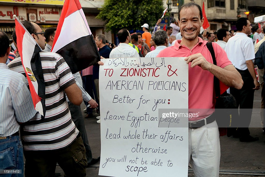 An Egyptian protester poses with a placard during a demonstration against deposed president Mohamed Morsi on July 7, 2013 in the northern Egyptian city of Alexandria. In the capital, opponents of Morsi packed Tahrir Square in their tens of thousands to show the world his ouster was not a military coup but the reflection of the people's will. AFP PHOTO/ STR